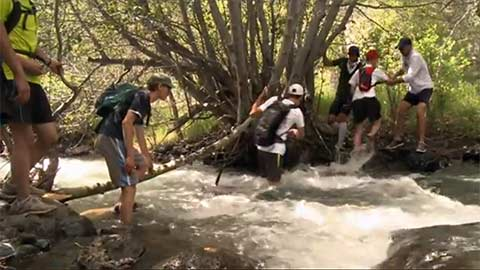 Teenagers help each other cross a swift-moving stream.